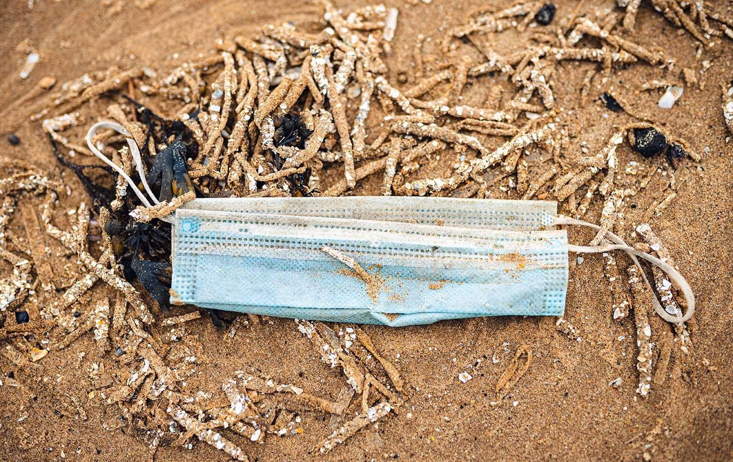 Weggeworfene Maske an einem Strand