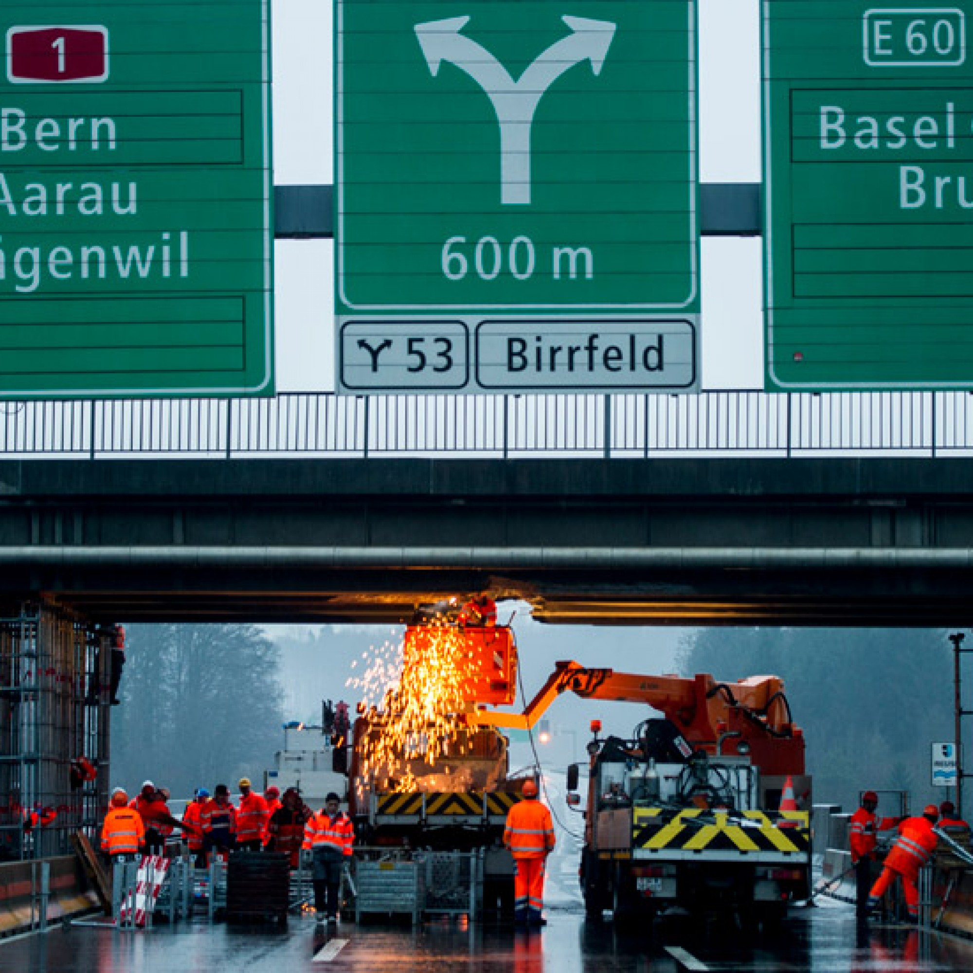 Arbeiter sichern die Bruecke nach einem Lastwagenunfall auf der A1 von Zuerich Richtung Bern/Basel, aufgenommen am Montag, 13. Januar 2014 in Birmenstorf AG. Ein mit einer Baumaschine beladener Anhaengerzug kollidierte in Fahrtrichtung Bern mit der Ueberf