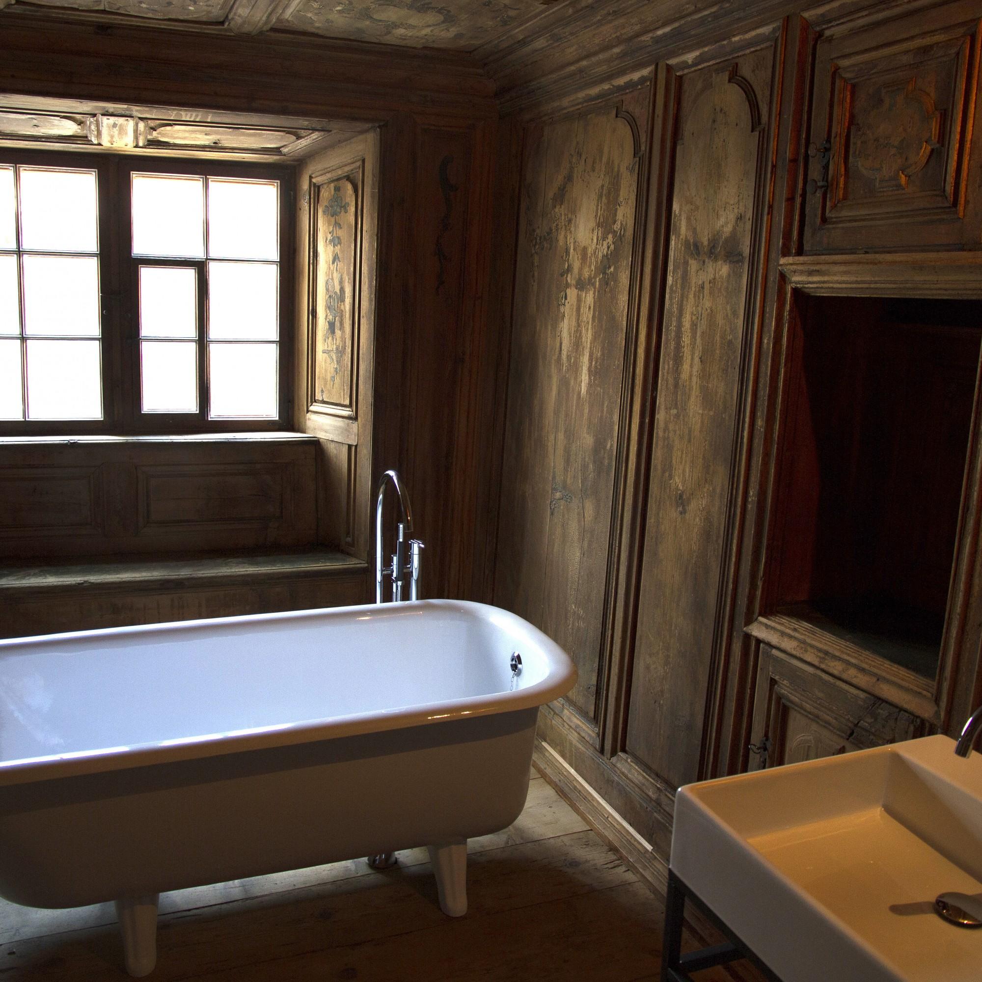 Im Bad kontrastieren dit barockes Täfer mit Badewanne und Lavabo. (Ferien im Baudenkmal)