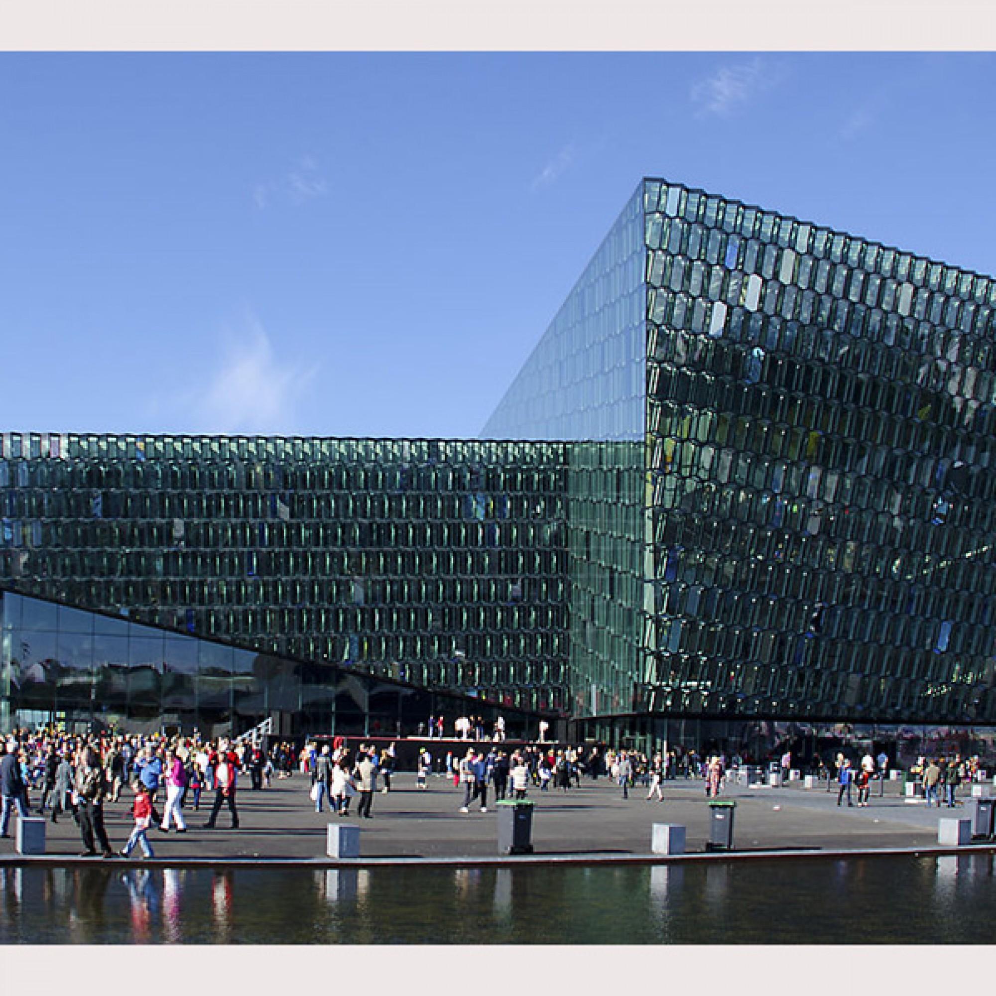 Harpa-Konzerthaus in Reykjavik mit seiner Fassade: Die Struktur aus dichroitischem Glas reagiert je nach Wetter auf die wechselnden Tageslichtfarben. (wikimedia.org, pjyt56, CC)