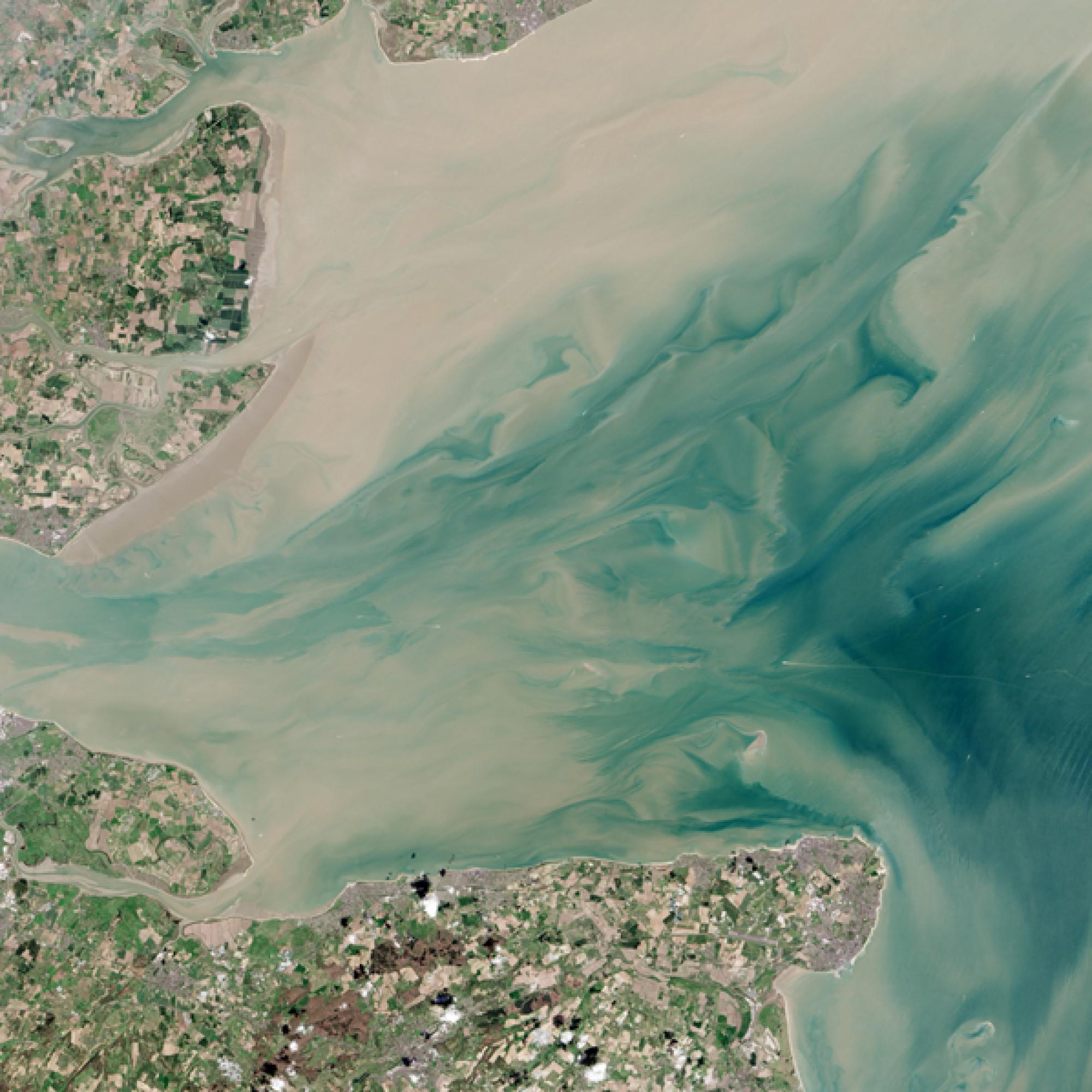 Und vor der Küste Englands, bei der Themsemündung schimmern Land und Wasser in Pastelltönen. (Nasa)