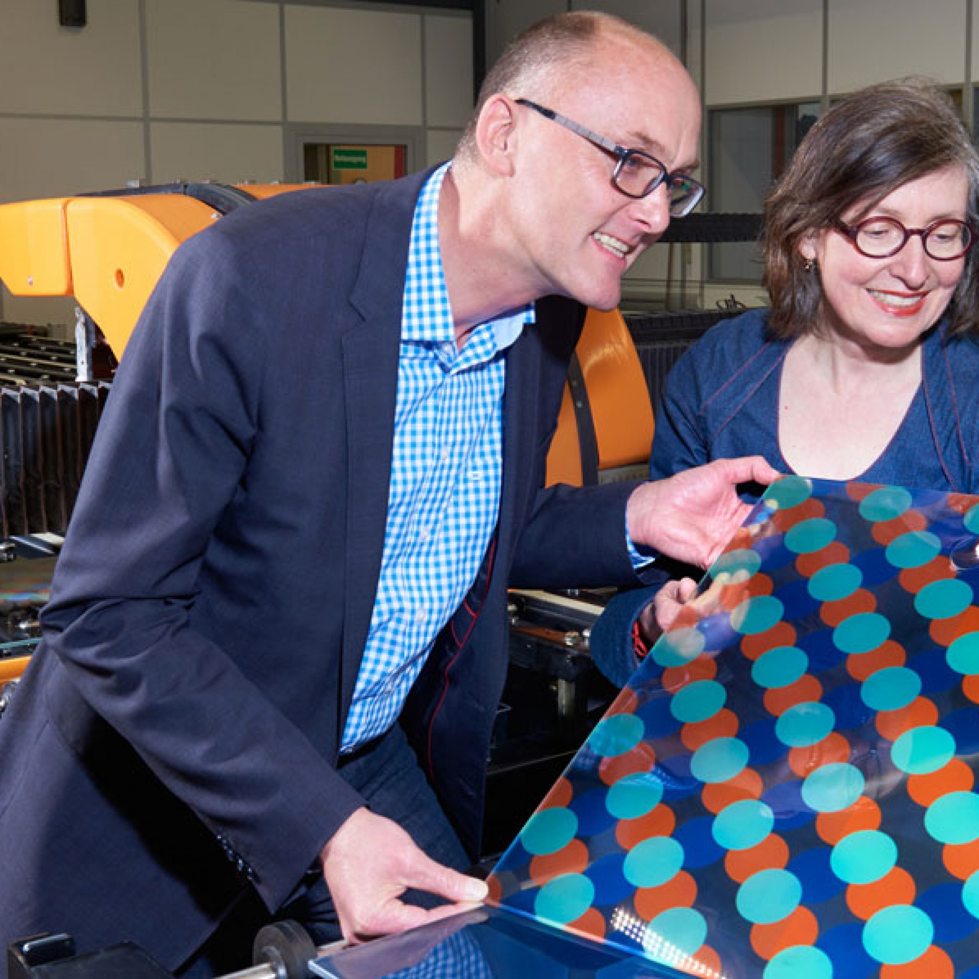 Monika Gold und Stephen Wittkopf von der Hochschule Luzern verfolgen den Druck eines Musters bei der Glas Trösch AG. (Doris Kuert/HSLU)