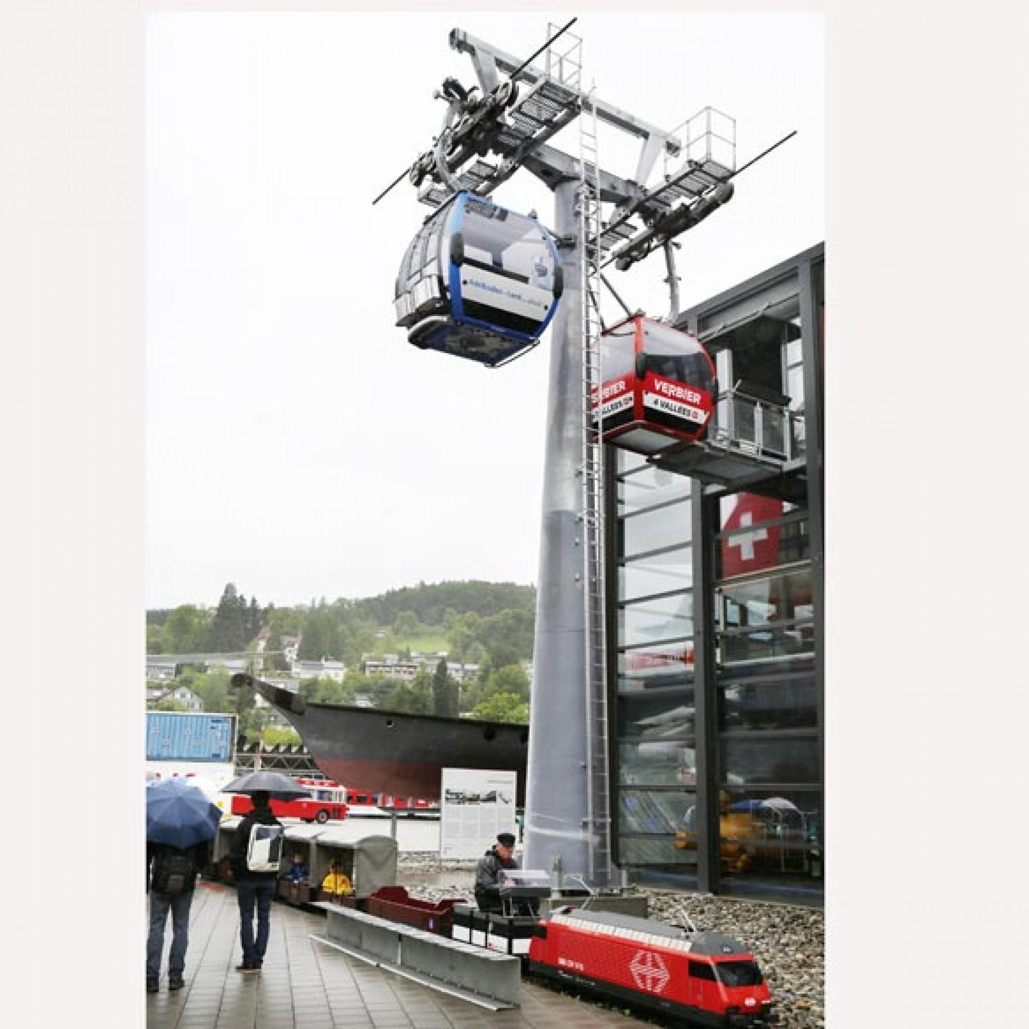 Vor der Halle Seilbahnen und Tourismus steht ein Original-Seilbahnmast mit zwei  Gondeln. (Foto: Verkehrshaus der Schweiz/Christen)
