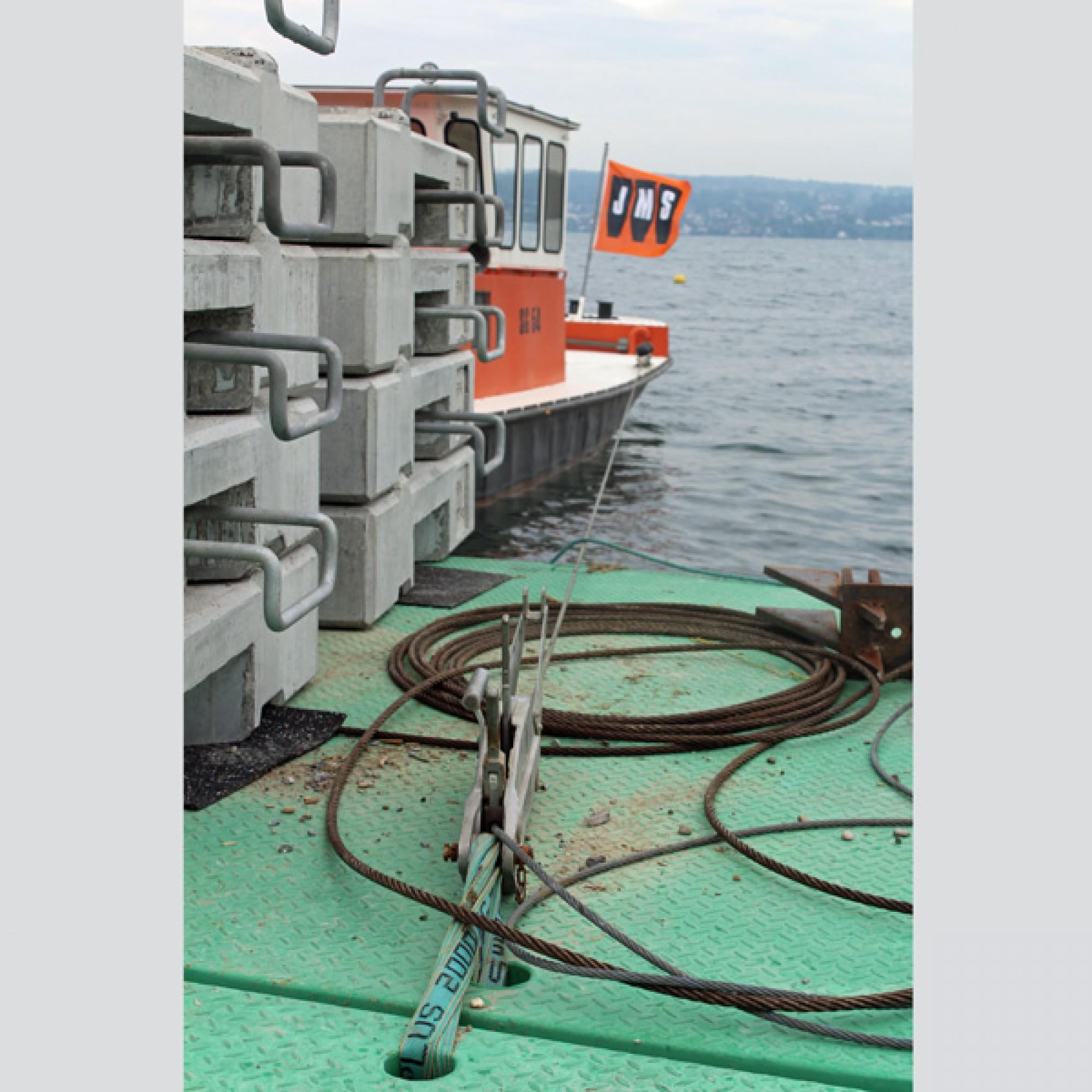"""Der Ponton ist mit Stahlseilen am Motorboot """"Neptun"""" festgemacht, das die Fracht über den See bringen wird."""