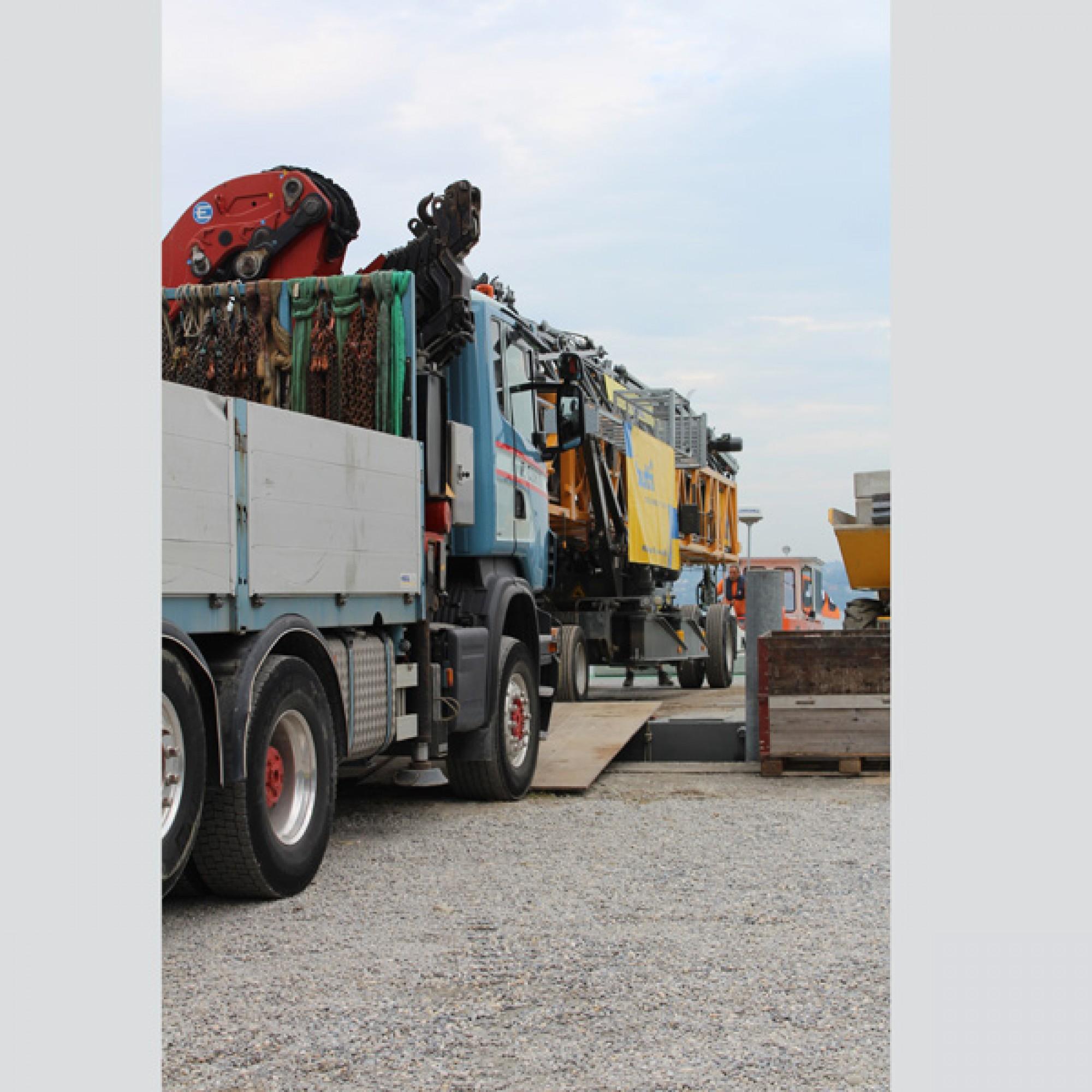 Ein LKW schiebt das tonnenschwere Baugerät auf den Ponton.