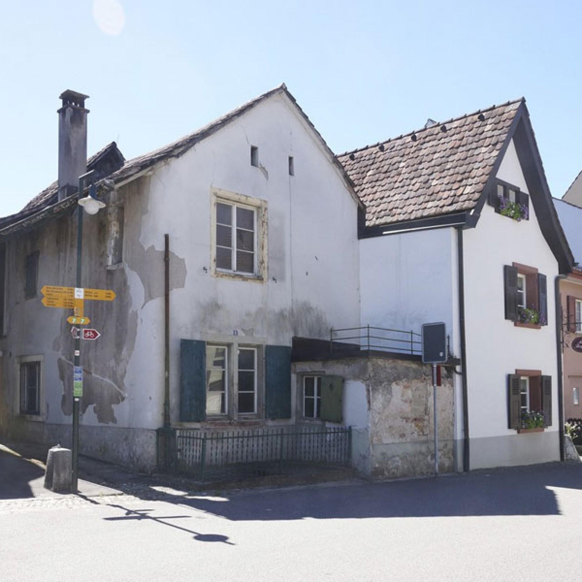 1/2 Das Haus an der Burggasse in Muttenz (Bildmitte). Das Nachbargebäude ist konstruktiv mit ihm verbunden, archäologisch jedoch nicht untersucht (Archäologie Baselland)