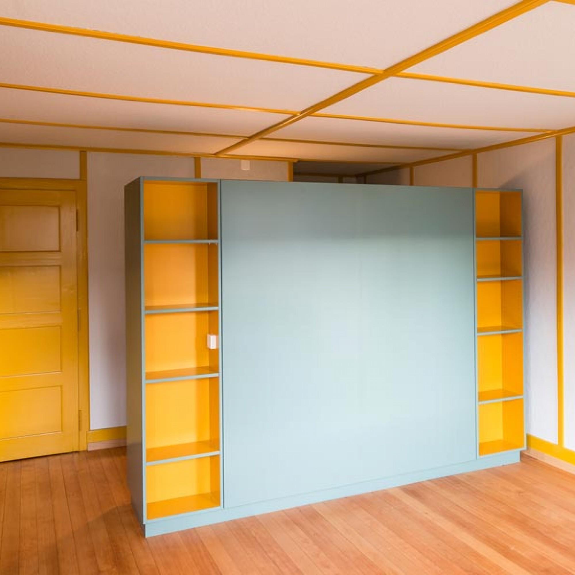 Der Raum im Obergeschoss wurde in Anlehnung an den originalen Zustand umgestaltet, die ursprünglich unbehandelte Pavatexverkleidung gestrichen. Ein neuer Einbauschrank ist frei in den Raum gestellt.