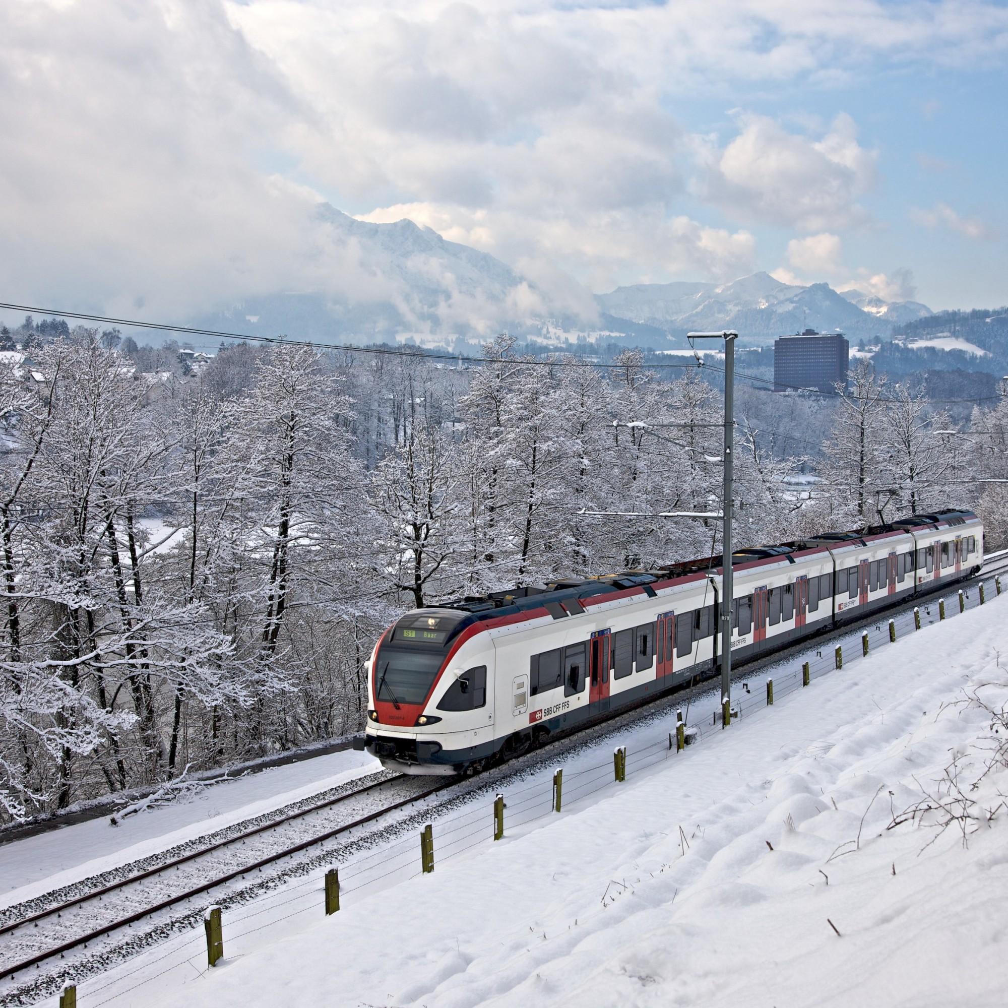 Der Zug RaBe523 der Stadtbahn Zug fährt entlang des Rotsees durch die Winterlandschaft.
