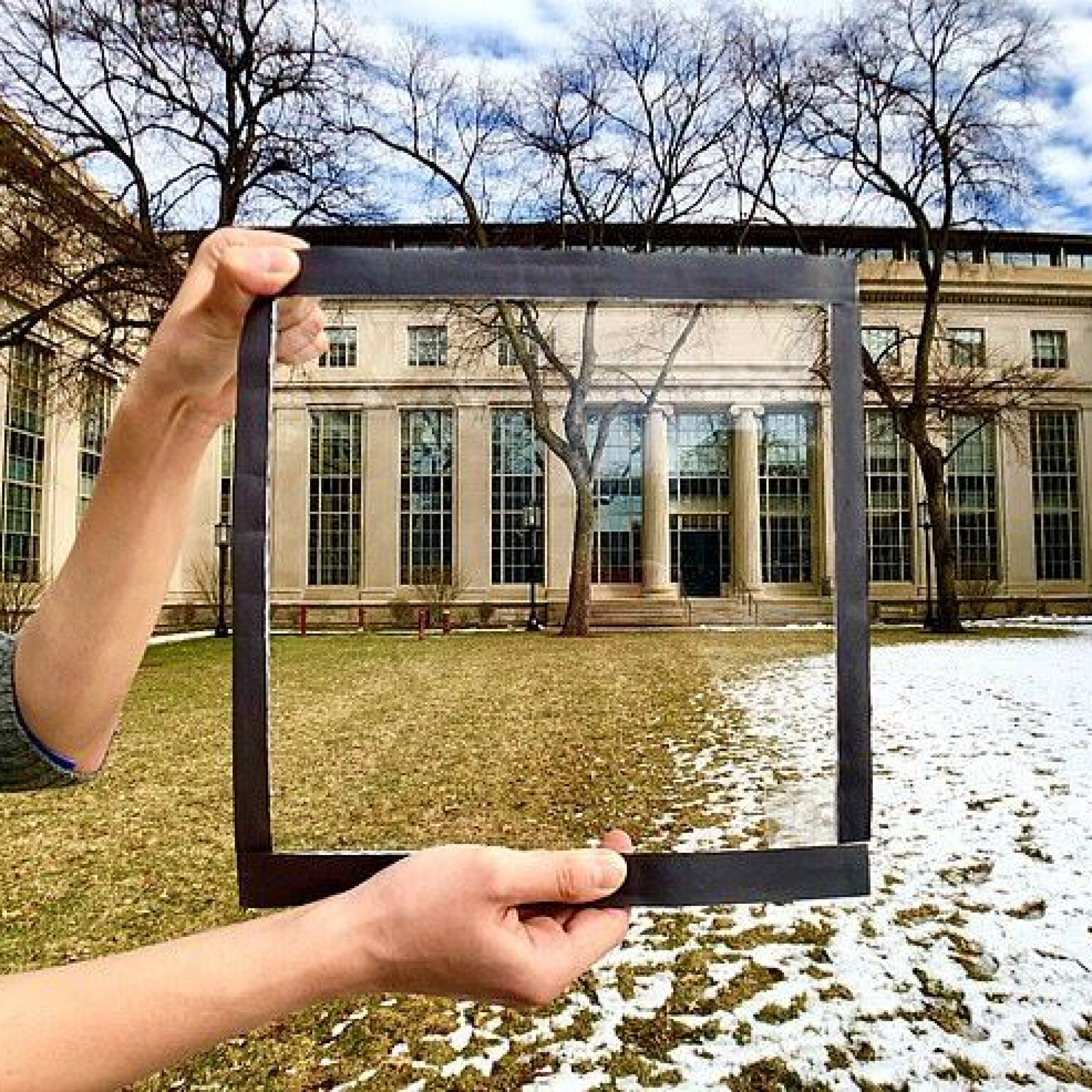 Mann hält Fensterglasscheibe mit Wärmeschutzfolie darauf, im Hintergrund ein Hof