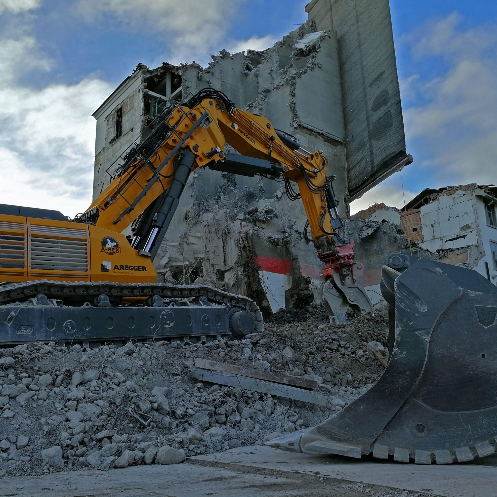 Die monströse Baggerschaufel wartet auf ihren Einsatz, während der A-Rex M9300 Mauerstücke mit einer überdimensionalen Beisszange herausreisst.