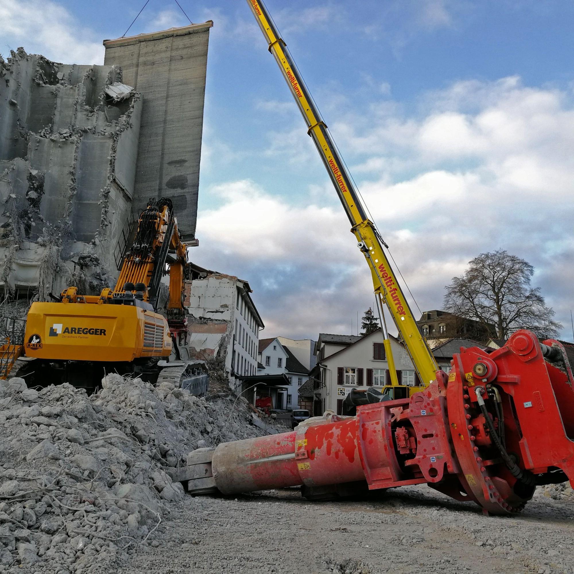 Ein Palfinger positioniert eine dicke Gummimatte als Schutz zwischen Abrissgebäude und dem angrenzenden Haus, das stehen bleiben soll.