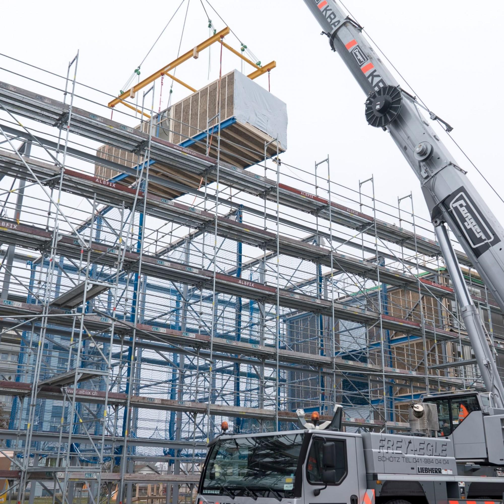 Während die Module noch in der Produktion stecken, wird in Lenzburg das Untergeschoss erstellt und die Stahlstruktur des Wohnhauses aufgebaut.