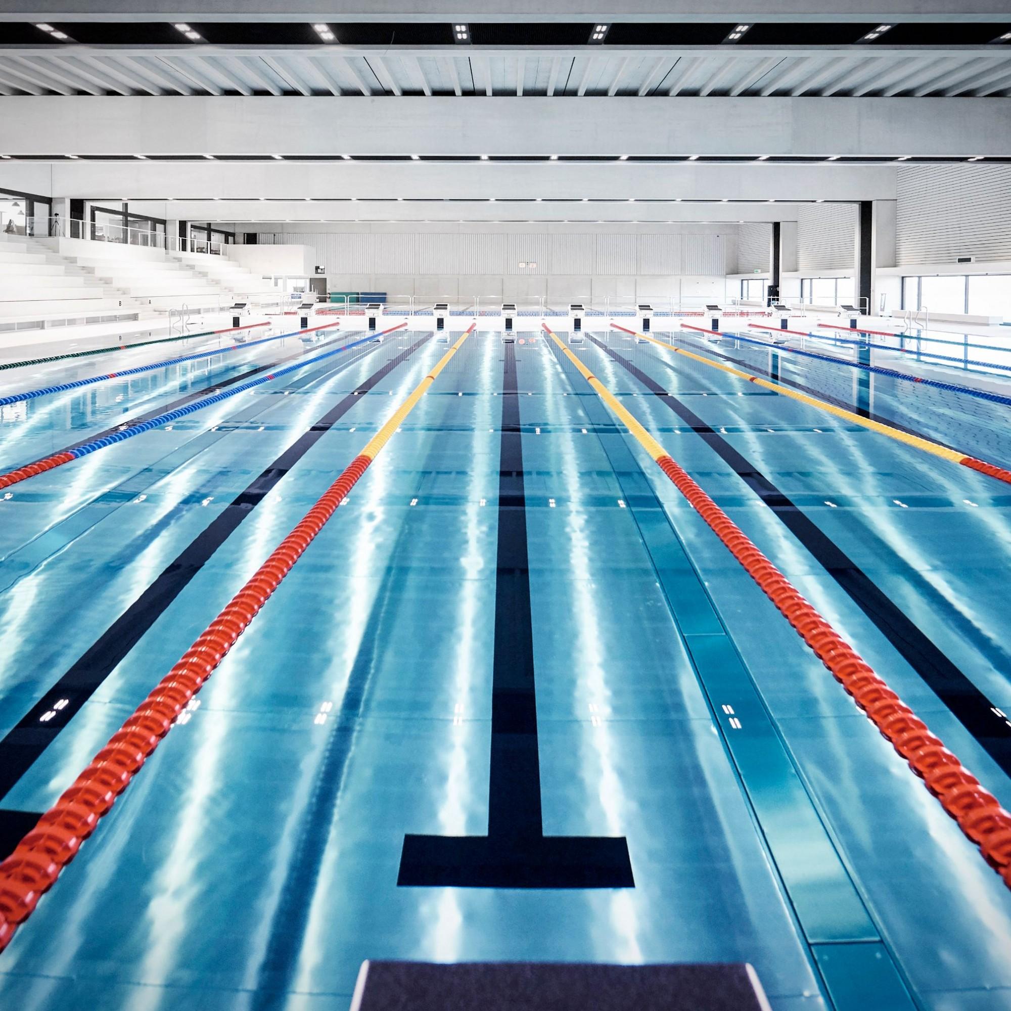 Die Schwimmarena bietet einen 50MeterOlympic Pool mit zehn Bahnen, verschiebbarer Startbrücke, Ertrinkendenerkennungssystem und Hubboden.