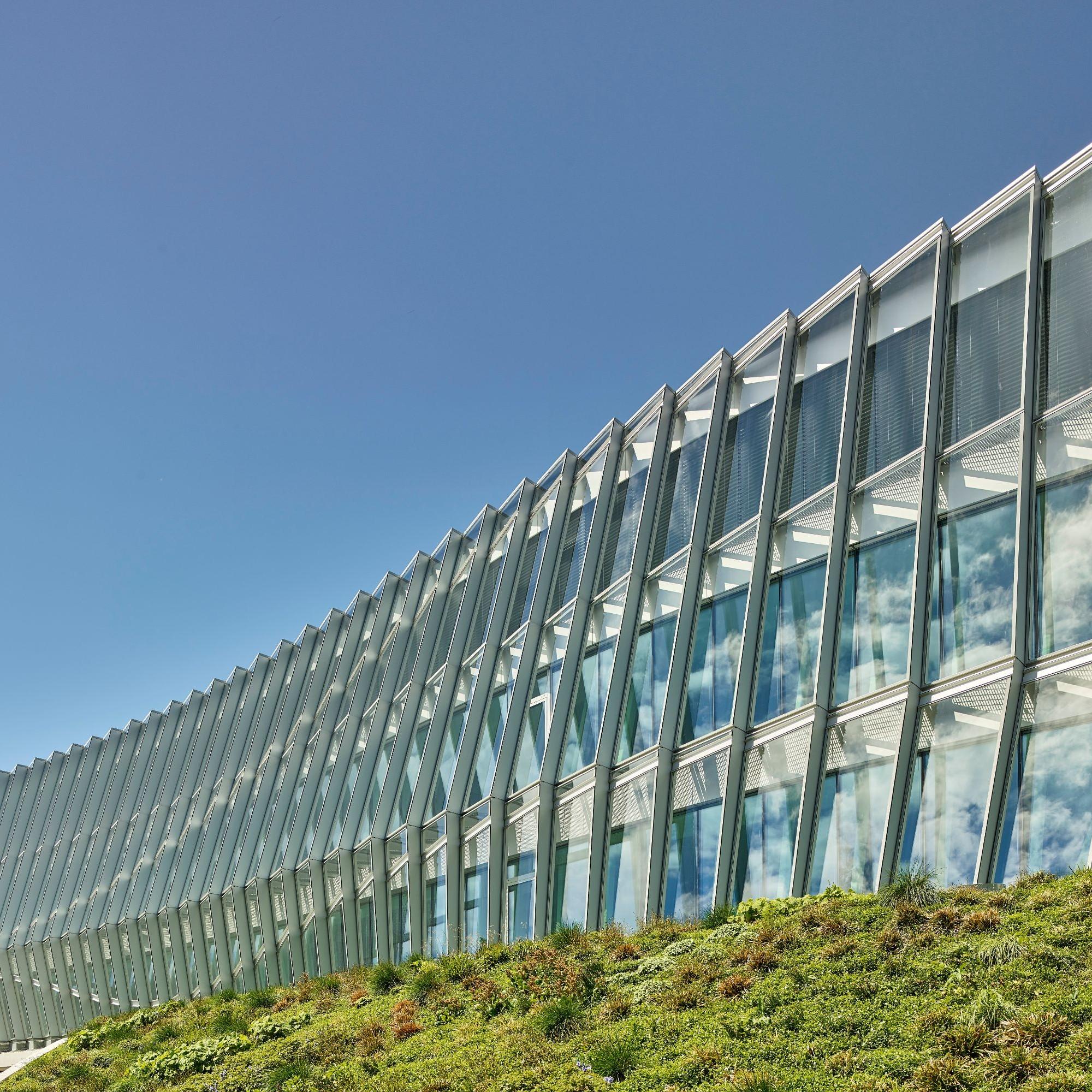 Die gewellte Glasfassade des Gebäudes scheint sich dauernd zu bewegen.