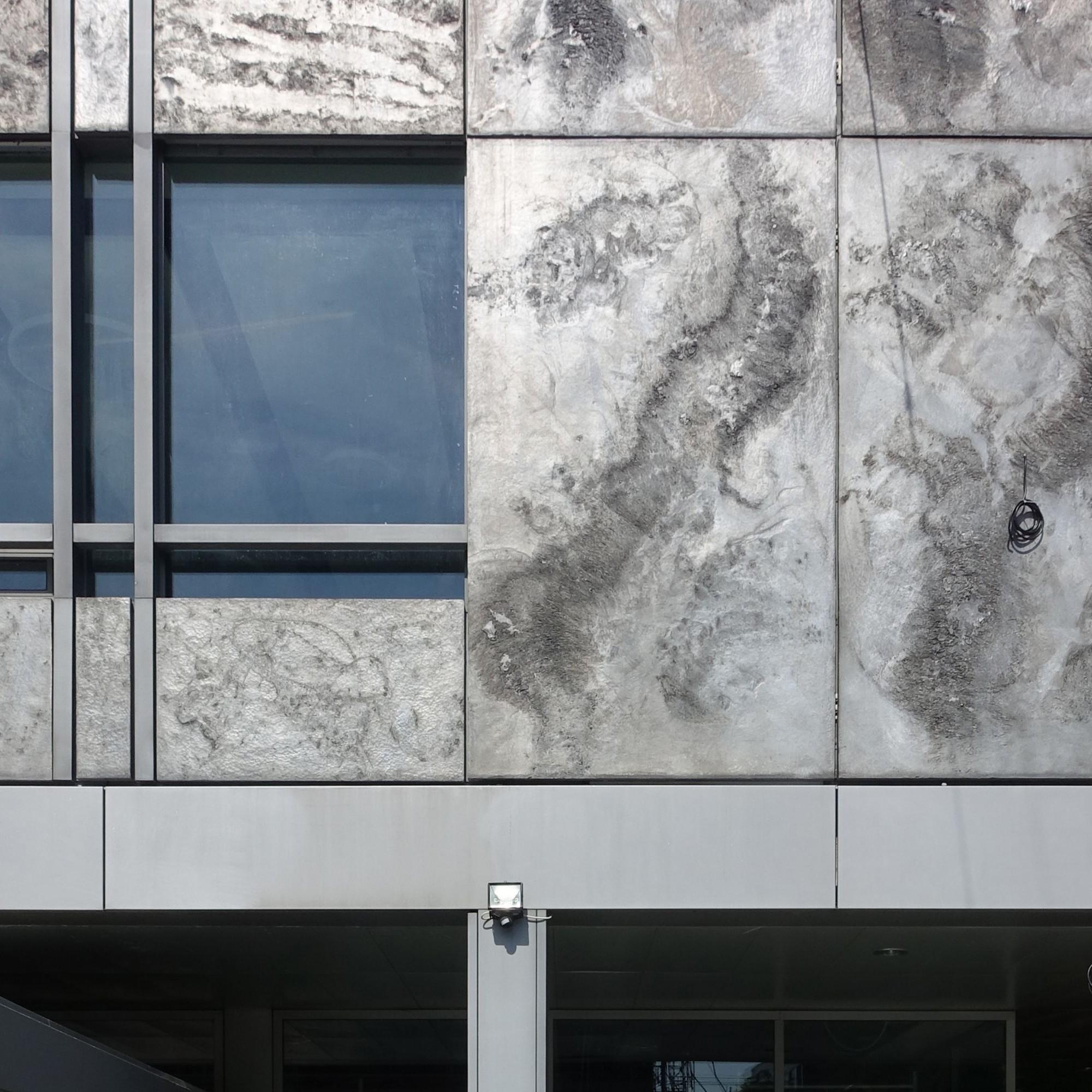 Die Rohaluminiumplatten erinnern an Mondlandschaften und ergänzen das rational aufgebaute Gebäude mit einem dekorativen Element.