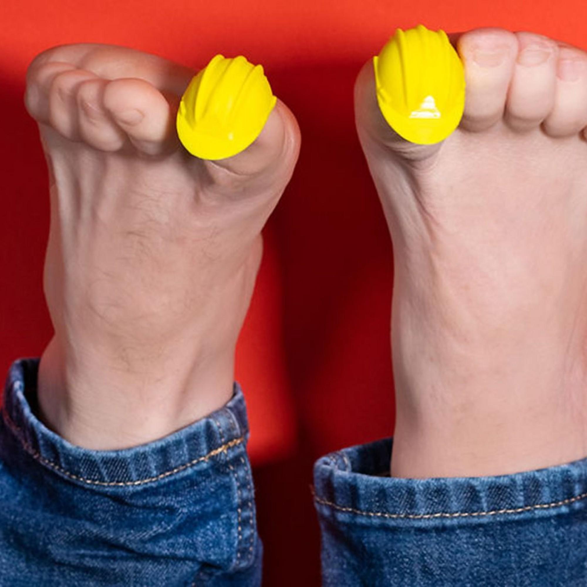 Gelbe Bauhelme auf Zehen