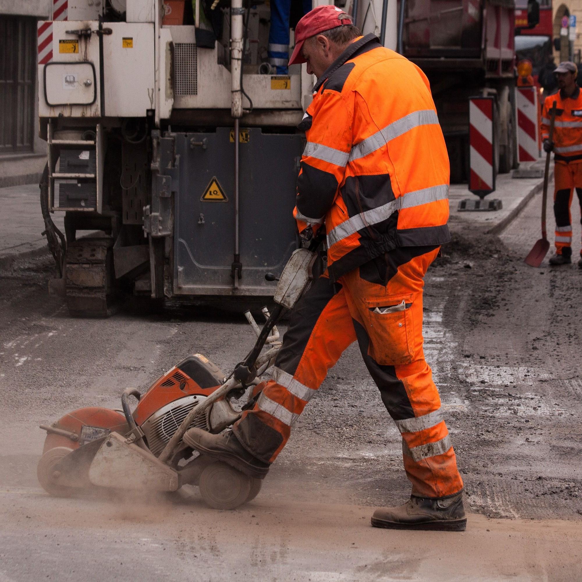 Strassenbau, Arbeiter mit Maschine