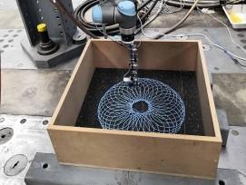 Roboterarm legt Strickmuster aus