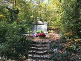Von Bäumen umgeben, wird dieser Stein eines Familiengrabes durch die Natur geschützt.