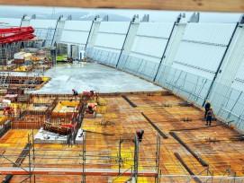 Kaskadenartiger Baufortschritt:Während auf der einen Seite die letzten Decken des Hochbaus armiert und gegossen werden, läuft auf der anderen schon der Einbau der Fassaden.
