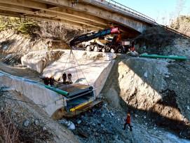 Zentimetergenauer Einbau der über siebenTonnen schweren Stahlkonstruktion in die Aussparung der aus Beton gefertigten Wildbachsperre unter der Kantonsstrassenbrücke über den Illgraben.