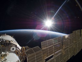 ISS über der Erde mit Sonne.