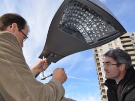 Gemeindevorstand Andreas Thöny (links) und Regierungsrat Mario Cavigelli montieren die letzte LED-Lampe.