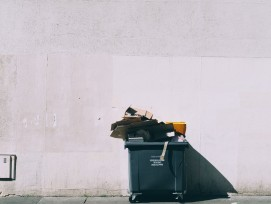 Übervolle Mülltonne vor weisser Wand