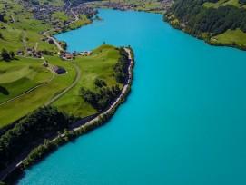 Atemberaubend blauer See mit grünen Matten und kleinem Dorf