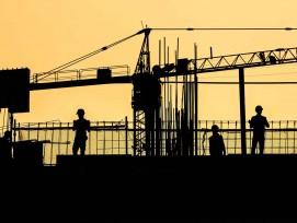 Silhouetten von einem Kran und Bauarbeitern