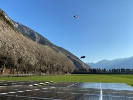 Helikopter fliegt Solarmodul vom Talboden in die Höhe.