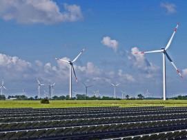 Solaranlage mit Windturbinen im Hintergrund.