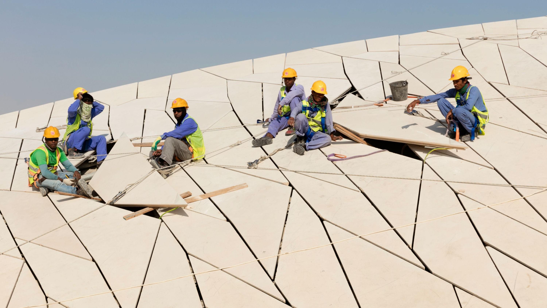 Arbeiter beim Einsetzen letzter Faserbetonelemente.